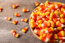 Bowl With Tasty Candy Corns On Wooden Table. Space For Text