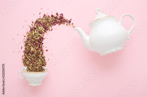 Dry herbal tea pouring from white porcelain teapot into cup on pink surface Canvas Print