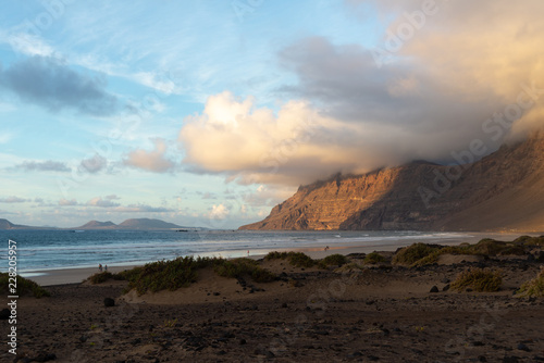 Foto op Canvas Diepbruine mountain with a cap of clouds on the ocean at sunset
