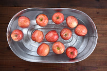 A Metal Tub Filled With Water And Apples For The Halloween Custom Of Apple Bobbing