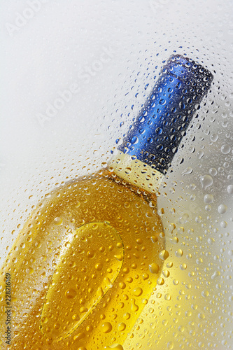 A white wine bottle behind glass with water drops