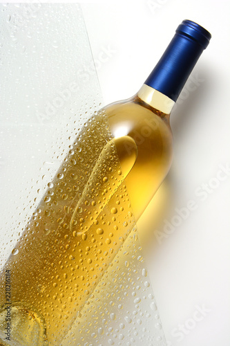 A white wine bottle behind a sheet of glass with water drops