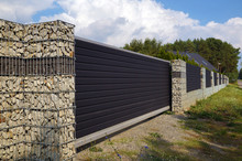 Wall. The Entrance Gate And A Very Long Fence Of The House Using Gabions.