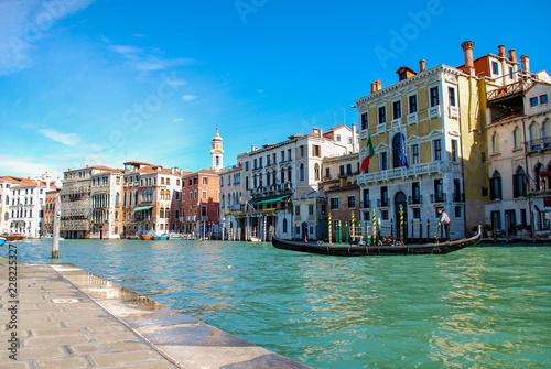 Foto op Plexiglas Venetie Gondola in front of Hotels on the Grand Canal in Venice Italy. Waterfront sidewalk in foreground.