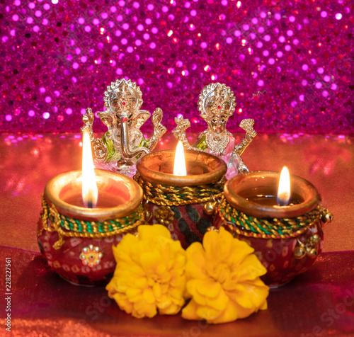 Diwali Background Showing Lit Lamps Against Idols of Deities Lakshmi and Ganesh