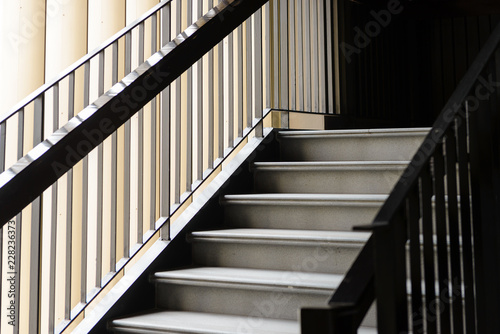 Photo Stands Stairs Empty Modern Concrete Staircase and black steel handrail with natural light, staircase in modern building - Dark Tone