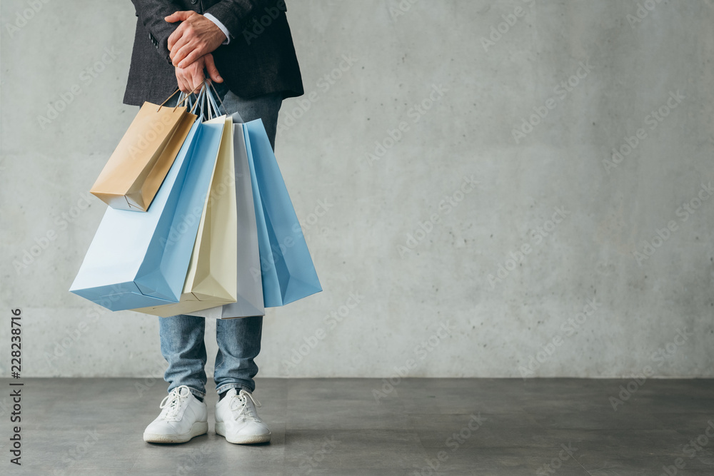 Fototapeta holiday sale. shopping and consumerism concept. man holding multiple bags with goods in hands.
