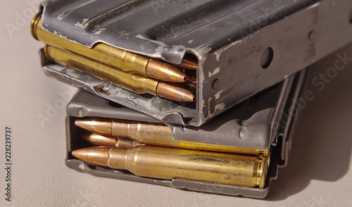 Photo Two metal rifle magazines, one stacked upon the other, loaded with