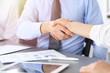 Close-up of business handshake at meeting or negotiation above the desk in office. Partners shaking hands while satisfied because signing contract or financial papers. Success concept