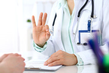 Doctor showing Ok sign to patient while sitting at the desk in hospital office, closeup of human hands. Medicine and health care concept