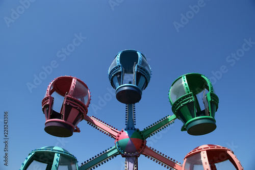 Poster Amusementspark Booths children carousel at the blue sky