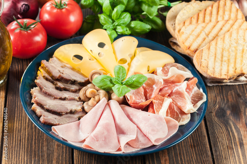 Tuinposter Assortiment Cold meat platter with ham, prosciutto, bacon and cheese