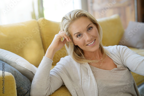 Fotografia  Portrait of attractive blond woman relaxing in sofa
