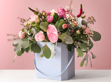 Gift Box With Beautiful Flowers On Table Against Color Background