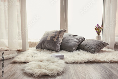 Fotografía  Cozy place for rest with soft pillows and furry rugs near window