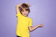 canvas print picture - Little boy in t-shirt pointing at something on color background