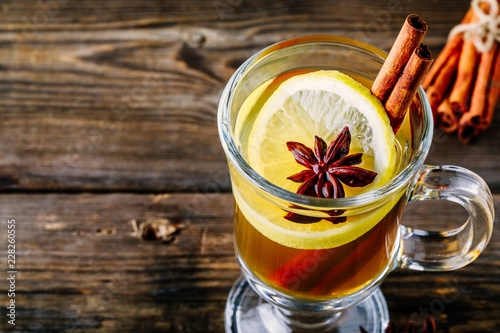 Recess Fitting Tea Hot spiced Apple cider Toddy with lemon, honey and cinnamon stick in glass on wooden background