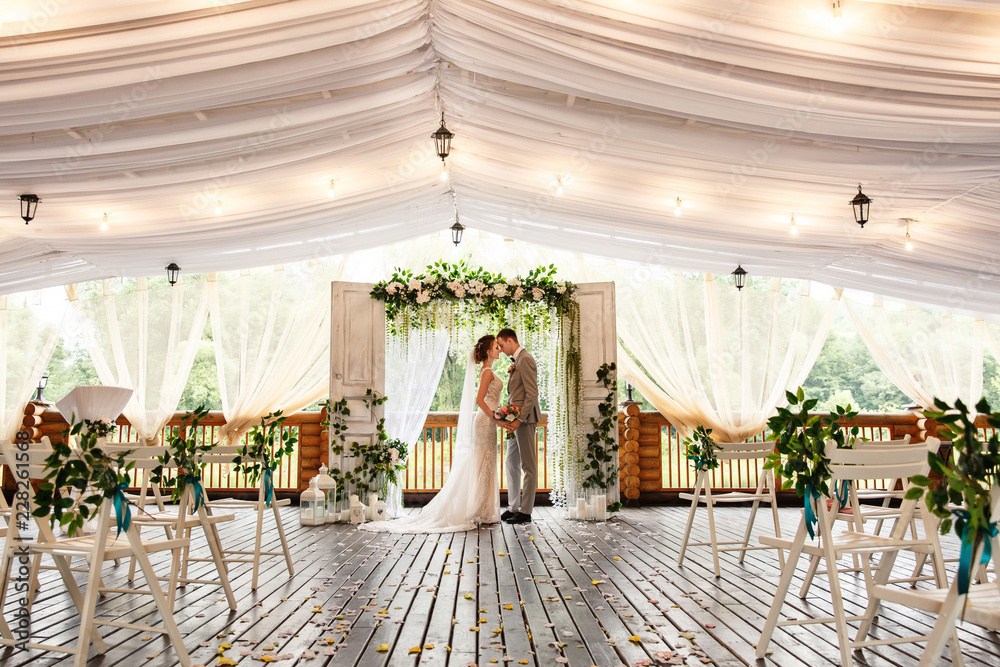 Fototapeta Wedding ceremony. Elegant wedding couple kissing near wedding arch, bride and groom in love