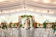 canvas print picture - Wedding ceremony. Elegant wedding couple kissing near wedding arch, bride and groom in love