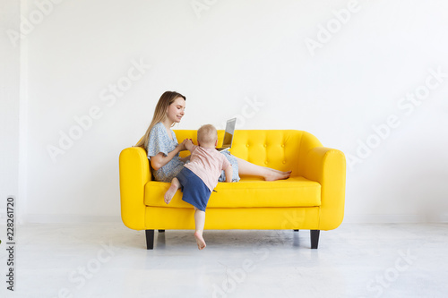 Obraz na płótnie Casual young mom designer sitting on yellow leather couch indoors white room wit