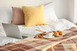 Wicker mat with delicious breakfast and laptop on bed