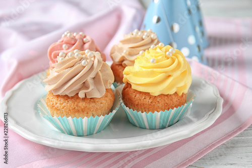 Photo  Plate with delicious cupcakes on white table