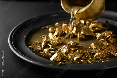 Pouring of water on plate with gold nuggets Canvas Print