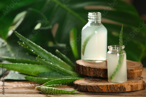 Fotografiet Bottles with fresh aloe vera juice on wooden table