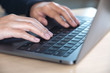Closeup image of hands using and typing on laptop keyboard on table