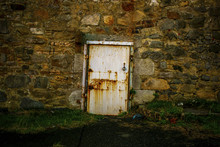 Romantic Nostalgic Decay White Door With Rust In A Massive Stone Wall With Grass Porch Travel Concept Tourism Landscape