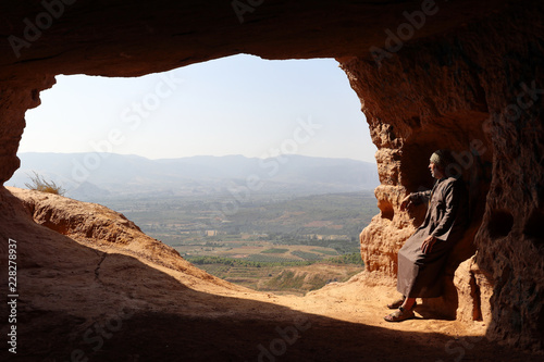 ISOLATED HERMIT SITTING AT THE ENTRANCE OF A CAVE ON THE HIGH OF A MOUNTAIN Wallpaper Mural