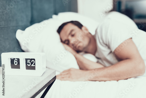 Valokuva  Person Sleeps Near Alarm in Bed With White Linens