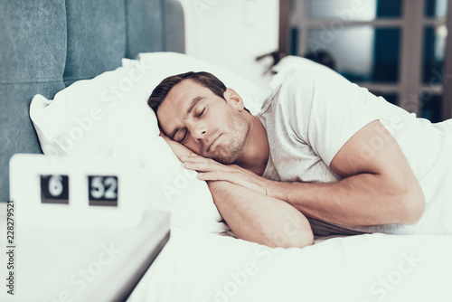 Foto  Person Sleeps Near Alarm in Bed With White Linens