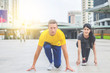 Young sport man and woman sitting in starting point for running in modern city background. Healthy couple doing exercise in the city. Lifestyle, sport and recreation concept. .
