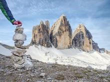Hiker Hand Building Stony Pyramid Bellow The Three Peaks Of Lavaredo.