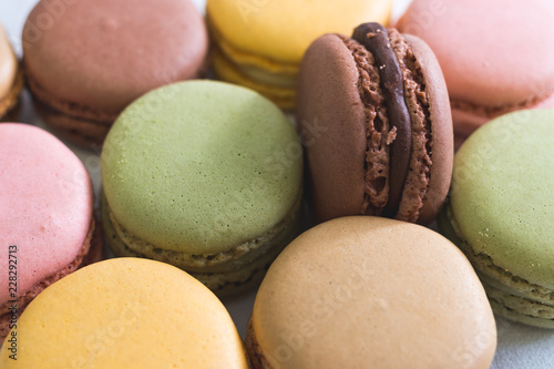 Background of colorful macarons of different flavors with one vertical brown