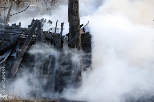 Foto auf Acrylglas Wald im Nebel conflagration. ruins and remains of a burnt wooden house. Burnt charred firewood in thick smoke.