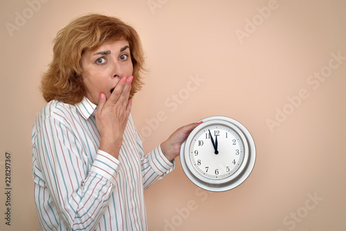 Fotografie, Obraz  Surprised and scared middle aged woman holding a big clock