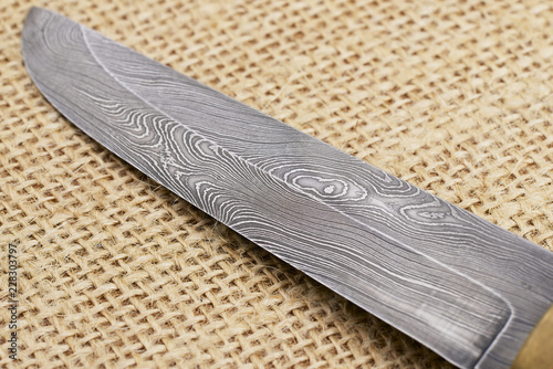 Fotografia Traditional handmade Finnish knife with the abstract wave pattern of damascus steel over an old sack background