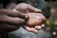 Man Rubbing A Stone To Extract...