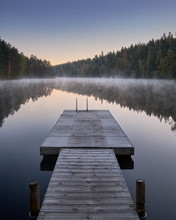 Scenic And Idyllic Lake Landscape With Pier And Fog At Autumn Morning In Finland