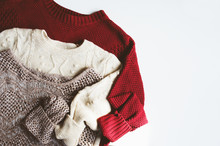 Set Of Warm Knitted Sweaters On White Background With Copy Space. Seasonal Autumn Or Winter Sale And Shopping Concept
