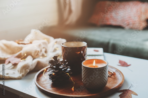 cozy autumn or winter morning at home. Still life details with cup of tea, candle, sketch book with herbarium and warm sweater. Scandinavian hygge concept