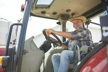 Portrait Of Smiling Senior Farmer On Tractor