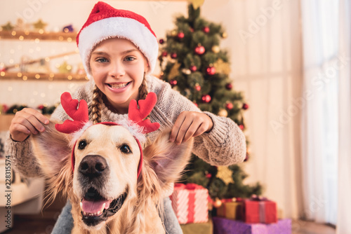 Fotografia  smiling kid in santa hat and golden retriever dog with deer horns having fun at