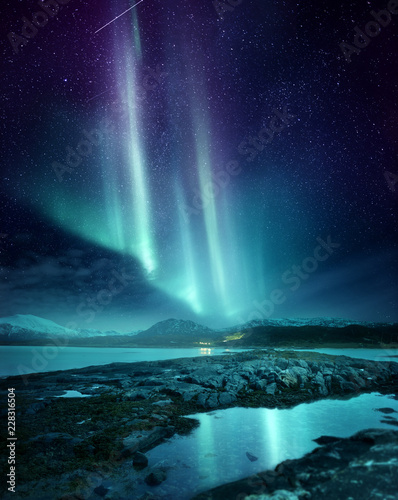 Foto auf Gartenposter Nordlicht A spectacular Northern Light Aurora display lighting up the night sky in Northern Norway. A popular destination within the arctic circle for hunting the Northern Lights. Photo Composite.