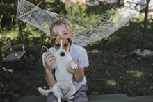 Portrait Of Boy With Dog Sitting In Garden