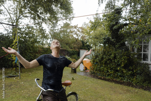 In de dag Tuin Mature man with bicycle enjoying summer rain in garden