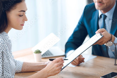 Fotomural  cropped shot of lawyer holding clipboard and young woman signing document