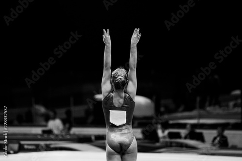 Foto auf AluDibond Gymnastik back female gymnast beginning of performing black-and-white photo